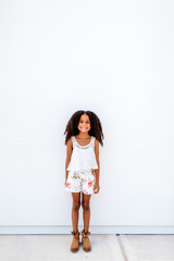 A little girl standing against a white background
