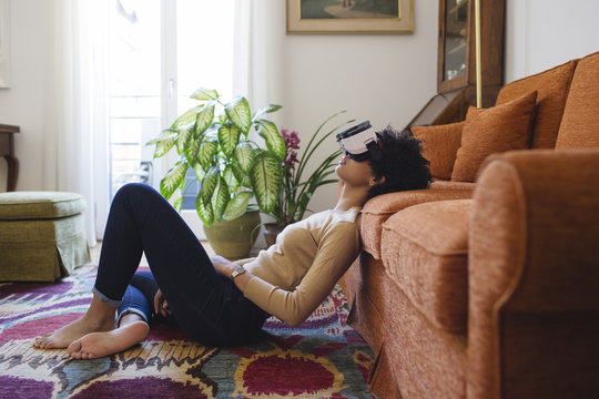 Woman sitting on the carpet with virtual reality headset