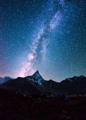 Milky way on a night sky over the mountains