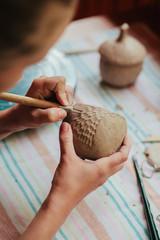 Woman potter making pattern on a ceramic mug