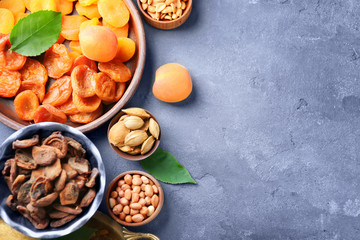 Dried apricots and nuts in different dishes on color background