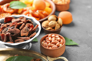 Dried apricots and nuts in different dishes on table