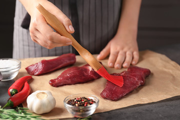 Woman applying oil onto raw steak with silicone brush in kitchen