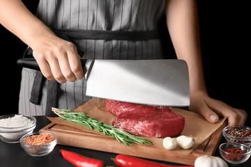 Woman cutting raw steak on kitchen table
