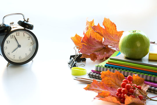 Colorful school supplies, book, and alarm clock on white. Top view, flat lay. Top view, copy space. Back to school.