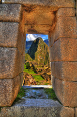 Colorful HDR image of the ruins of Machu Picchu near Cusco, Peru through a window in a temple, selective focus