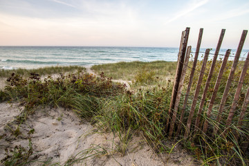 Coastal Beach Backgrounds. Dune grass, sand dunes, wooden fence and a winding sandy trail to the waters edge on the coast of Lake Huron. Rogers City, Michigan.