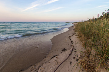 Sandy Beach Sunset Background. Wide sandy beach with surf on the shore of Lake Huron and sunset horizon in the background. Color image in horizontal orientation with copy space in the foreground.
