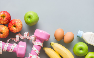Fitness and healthy active lifestyle background concept. Dumbbell, measuring tape, eggs, bananas, milk bottle on clean background. Top view with copy space.