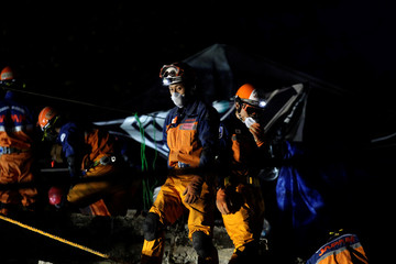 Members of a Japanese rescue team work at the site of a collapsed multi family residential building after an earthquake in Mexico City, Mexico