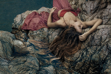 beautiful young woman in red dress laying down in water