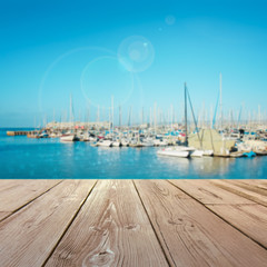 wooden table top with blurred harbor background