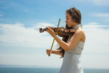 Girl playing violin at the beach in blue 2