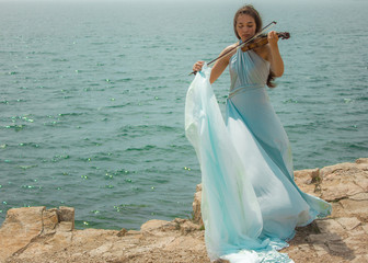 Girl playing violin at beach 1