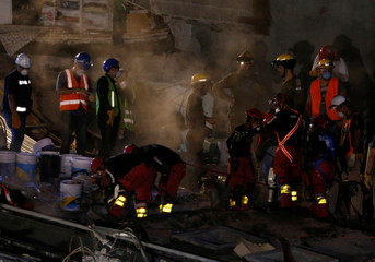 Members of rescue teams search for survivors in the rubble of a collapsed building after an earthquake in Mexico City