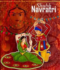 Couple performing Garba dance in Dandiya Raas for Dussehra or Navratri