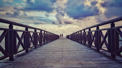Love couple watching the sea sunrise on wooden jetty
