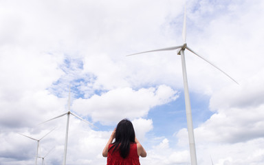 Traveler asian woman taking a photo with smartphone at wind turbines,Thailand