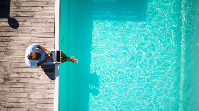 top view of well dressed male sitting at the pool with laprop and working