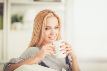 Young woman resting on couch and drinking tea in light room