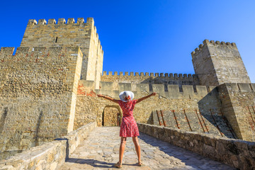 Happy woman with open arms in front of entrance of Sao Jorge Castle, at Moorish castle on highest hill in Alfama District. Female tourist enjoys of Lisbon's most popular tourist attraction.