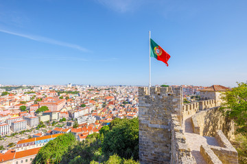 Lisbon aerial view cityscape with Portugal flag waving on ancient fortress wall of Sao Jorge Castle, at Moorish castle on highest hill in Alfama. Lisbon Castle is a popular tourist attraction.