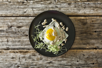Healthy breakfast. Fried egg on a black plate with micro-green and quinoa. Top view, closeup.