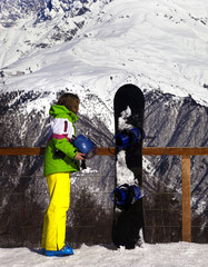 Young snowboarder with helmet in hands and snowboard on viewpoint in winter mountains
