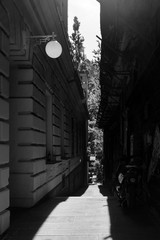 High contrast street photo European capital Ljubljana strong hard shadow passage alley