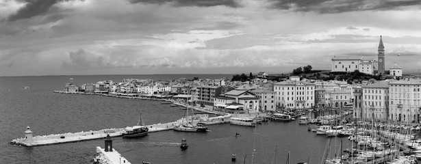 Panorama of Adriatic town Piran by the sea bay area boats and stone pier small lighthouse stone buildings European travel tourism