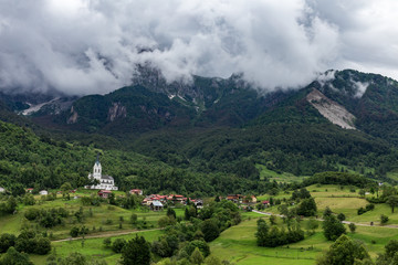 Church standing on the mountain slope under the clouds in small slovenian rural village over the green field