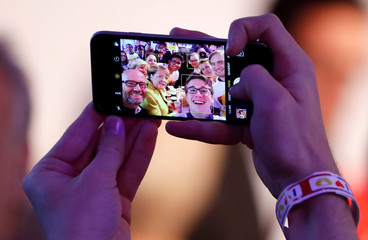 German Chancellor Angela Merkel is pictured on a mobile phone as she attends a breakfast with supporters at the CDU party election campaign meeting centre in Berlin