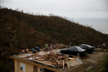 People stay at the roof of a damaged house after the area was hit by Hurricane Maria in Yabucoa