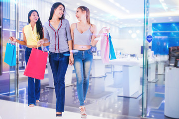 woman friends holding shopping bags excited to shopping in the shopping mall