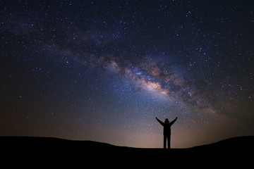 Landscape with milky way galaxy and space dust in the universe, Night sky with stars and silhouette of a standing sporty man with raised up arms on high mountain.