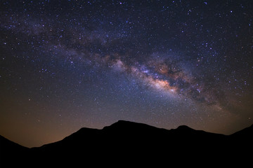 Beautiful milky way galaxy and silhouette of high moutain on a night sky before sunrise.