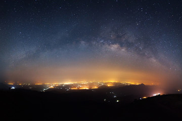 Starry night sky with milky way galaxy and city light at Phutabberk Phetchabun in Thailand.