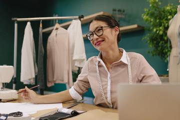 Smiling female dressmaker working at her desk