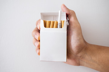 Hand holding cigarette box with hiding Marijuana rolled joint inside