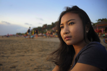 beautiful Asian lonely woman looking to infinity lost in her thoughts sad and thoughtful sitting on sand beach