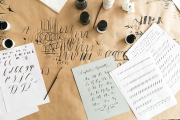 lettering, creation, work concept. paper with linens for training skills in calligraphy, black and white inks, brushes with thin tips and beautiful letters of english alphabeth written by designer