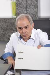 älterer Mann mit weißem Hemd  überreicht einen Aktenordner