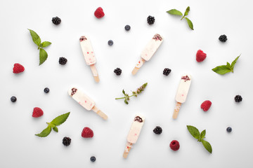 Homemade yogurt ice cream popsicles with mint and berries on a white background, top view.