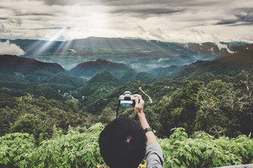Enjoy travel with peak of mountaon. A backpacker hand holding a digital camera at peak of mountain to take a photo of panorama mountain view with sunset light rays