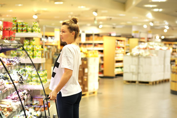 Woman shopping in supermarket reading product information. Checking list.Woman   choosing  a dairy products at supermarket