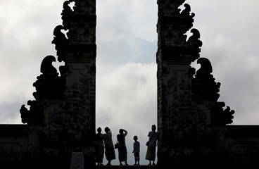 Balinese worshippers look at Mount Agung, enshrouded by clouds, from the gate of Penataran Agung Lempuyang temple, a day after the volcano's alert status was raised to the highest level, in Karangasem Regency, on the resort island of Bali