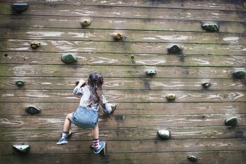 Little girl climbing the wall
