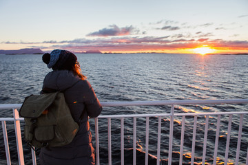 Woman traveler with backpack on the deck of a ferry in the Atlantic Ocean