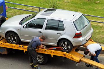 погрузка поврежденного неисправного легкового автомобиля на специальный тягач