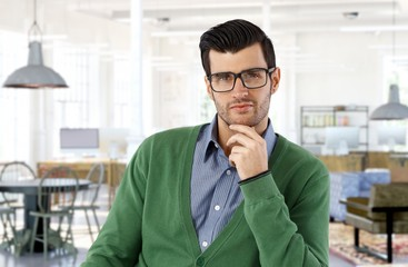 Portrait of young smart man in glasses at home